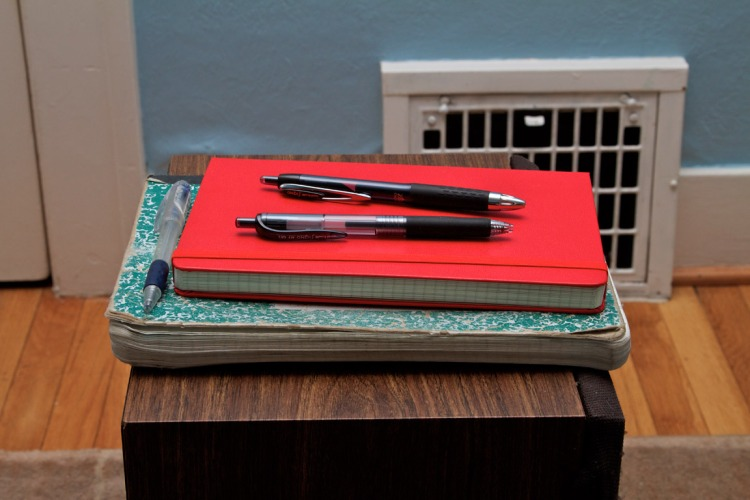 The new notebook and pens sitting on the old